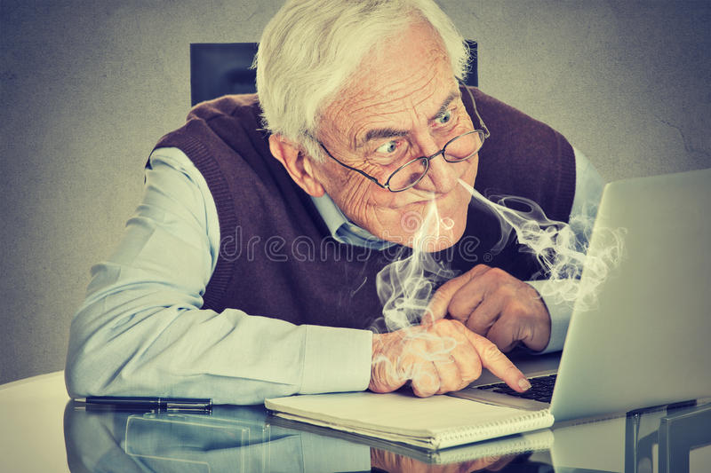 Stressed elderly man using computer. Blowing steam from nose frustrated sitting at table isolated on gray wall background. Senior people and technology concept stock photography
