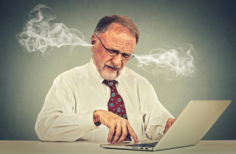 Stressed elderly old man using computer blowing steam from ears. Frustrated guy sitting at table working on laptop isolated on gray wall background. Senior royalty free stock image