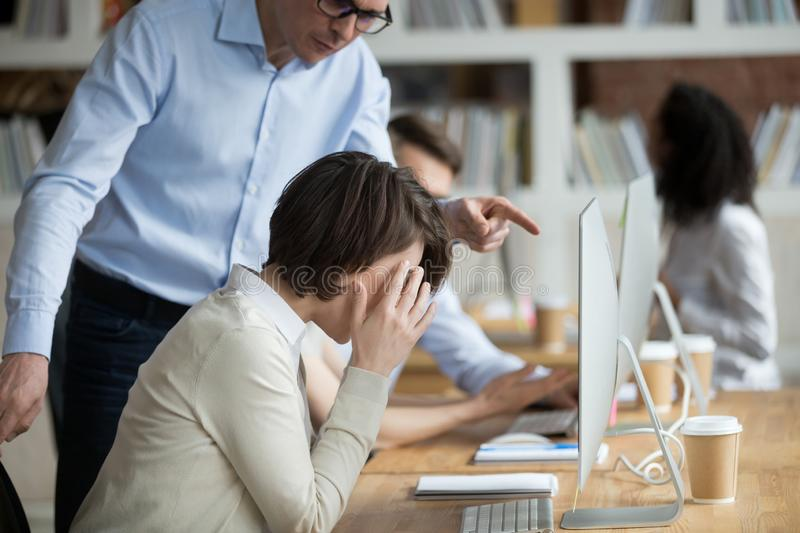 Stressed female employee suffering from discrimination of angry male boss stock images
