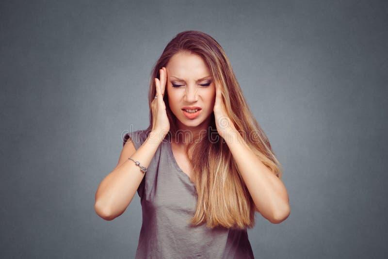 Stressed esgotou a mulher que tem a dor de cabeça de tensão forte fotos de stock