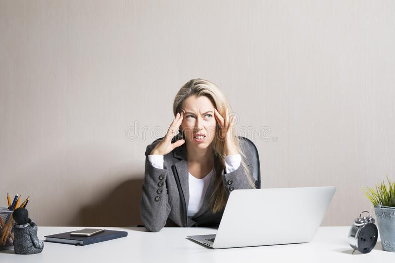 Stressed and exhausted woman sitting at office desk royalty free stock photography