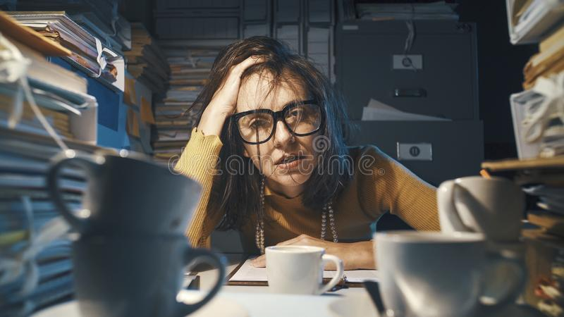 Stressed exhausted businesswoman working at night stock image