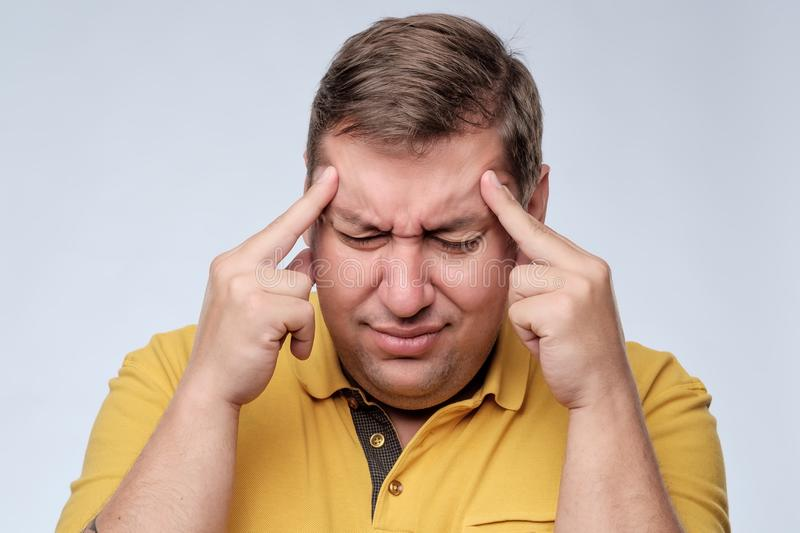 Stressed fat man in yellow t-shirt with fingers on temple suffering from headache. stock photography