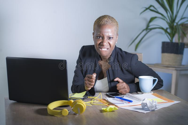 Stressed and frustrated afro American black woman working overwhelmed and upset at office laptop computer desk gesturing angry in royalty free stock photo