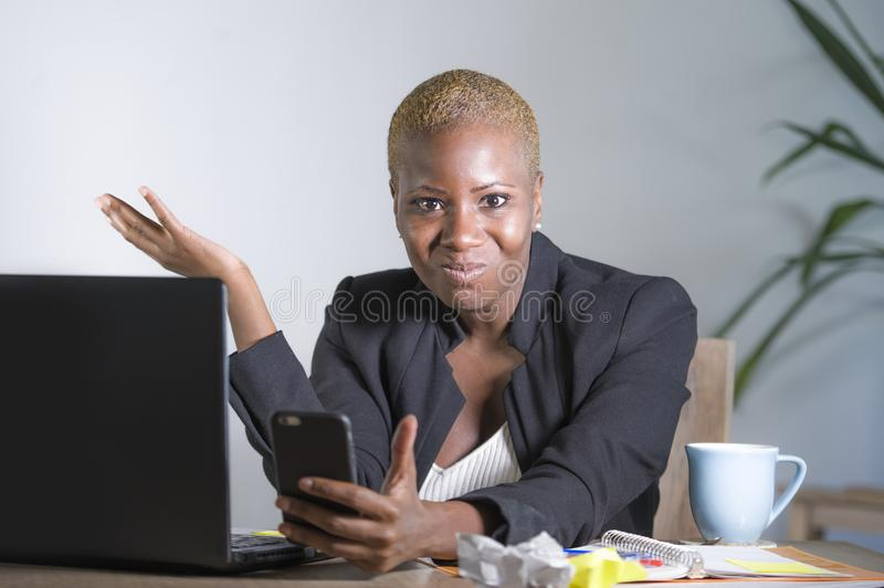 Stressed and frustrated afro American black woman working upset at office laptop computer desk gesturing angry looking at mobile p stock image