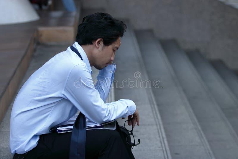 Stressed frustrou o homem de negócio asiático novo que senta-se na escadaria Ele que sente desapontado ou cansado com trabalho fotos de stock