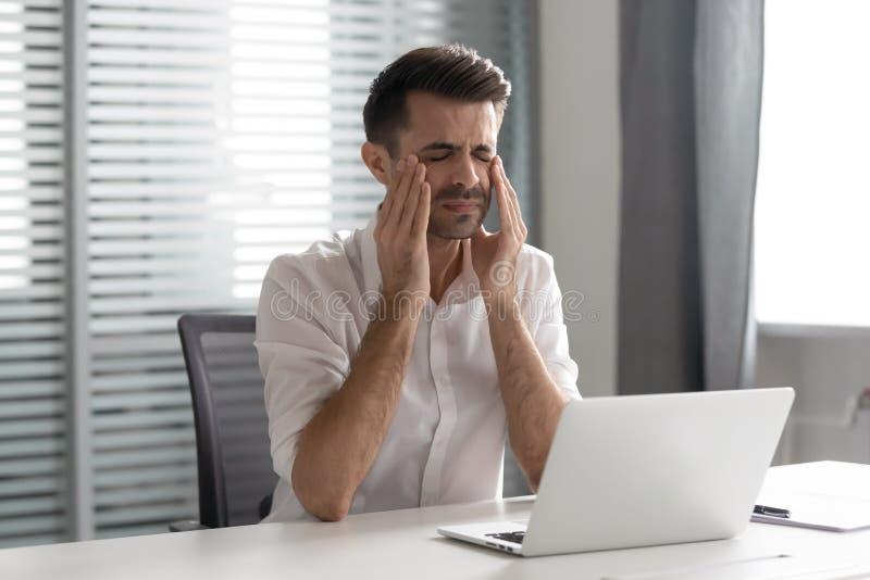 Stressed frustrou o homem de negócios sofre do ataque forte da dor de cabeça no local de trabalho foto de stock royalty free