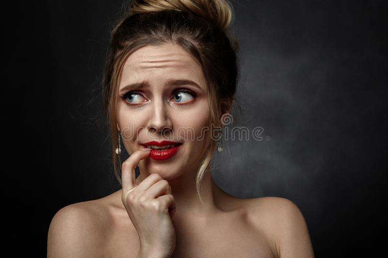 Stressed fun girl. With finger on mouth on black background looking aside stock photo