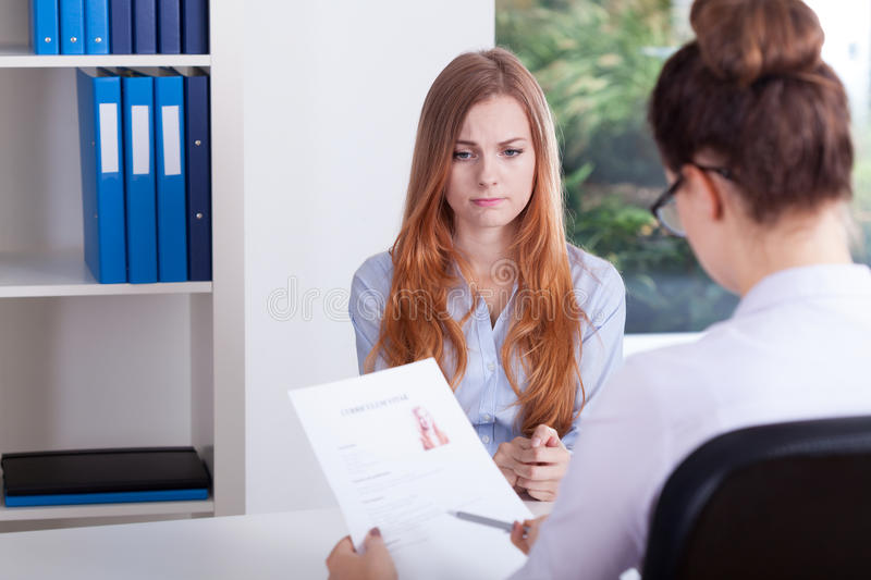 Stressed girl on a job interview royalty free stock image
