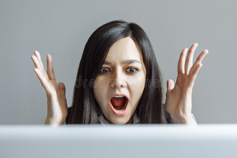 Stressed ha colpito la donna di affari che si siede alla tavola davanti al computer portatile che sembra la bocca spalancata sgom fotografie stock libere da diritti