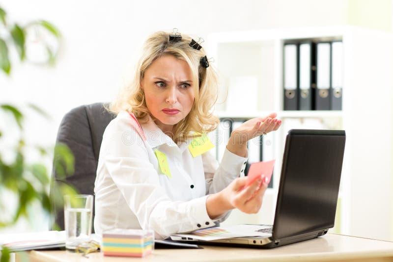 Stressed ha sovraccaricato la donna di affari che si siede allo scrittorio fotografia stock