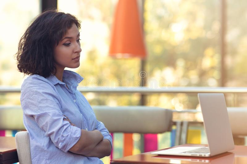 Stressed hipster businesswoman working on laptop in her office.  royalty free stock photo
