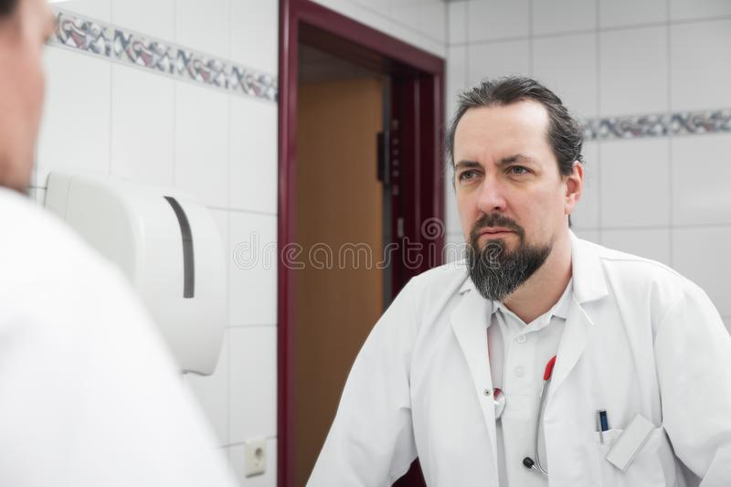 Stressed looking doctor in front of an mirror. Is watching himself stock photography