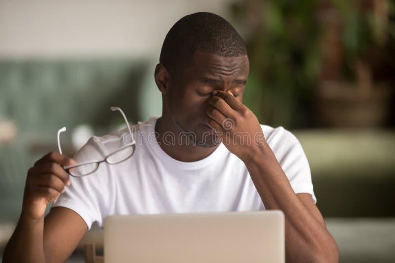 Stressed müde von der Computerarbeitsafrikanermanngefühls-Augenbelastung lizenzfreie stockfotos