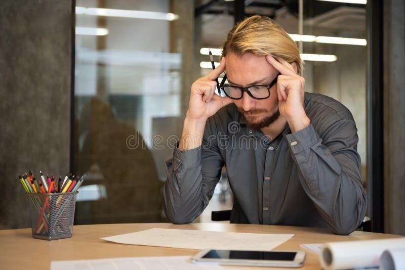 Stressed Male Creative Designer sitting and thinking stock image