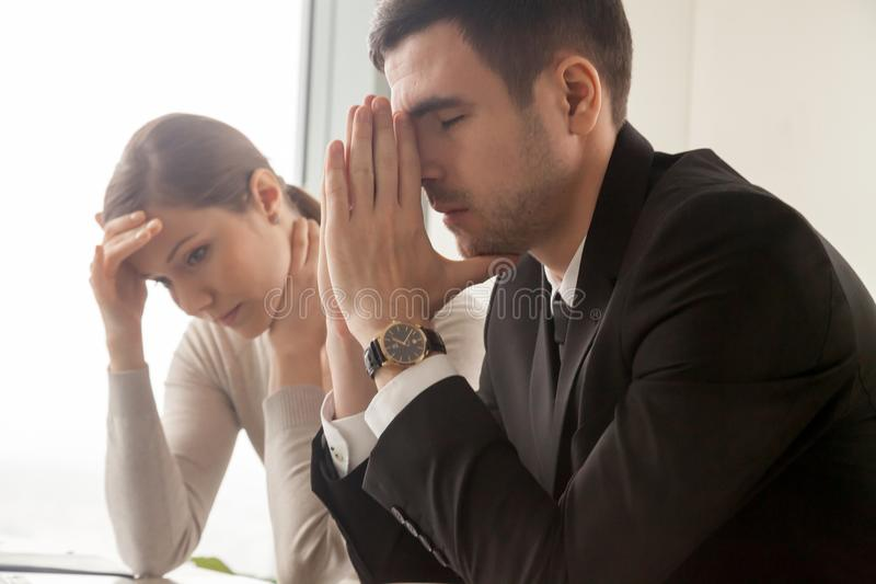 Young employees frustrated of difficulties on work. Stressed male and female business persons sitting at desk, hard thinking about problem. Businessman and stock photo