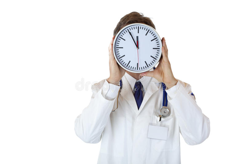 Stressed male medical doctor under time pressure. Stressed doctor with clock in front of face as sign of time pressure.Isolated on white background royalty free stock image
