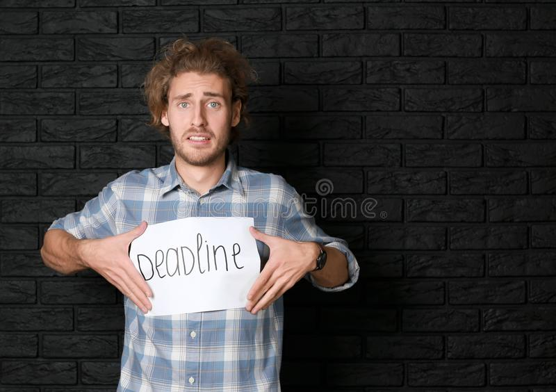 Stressed man holding sheet of paper with word DEADLINE on dark brick background stock photography
