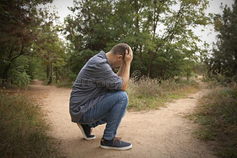 Stressed man sitting at crossroads. Concept of choice stock photos