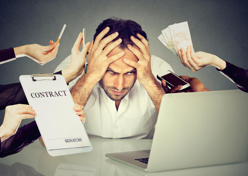 Stressed man sitting at his desk in front of computer stock image