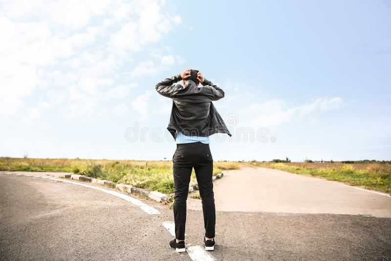 Stressed man standing at crossroads. Concept of choice stock photos
