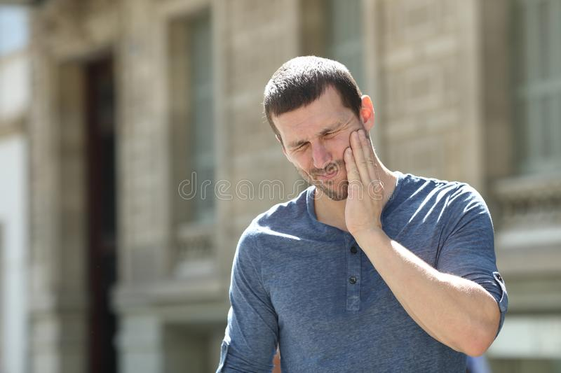 Stressed man suffering tooth ache in the street. Stressed man suffering tooth ache standing alone in the street royalty free stock photo