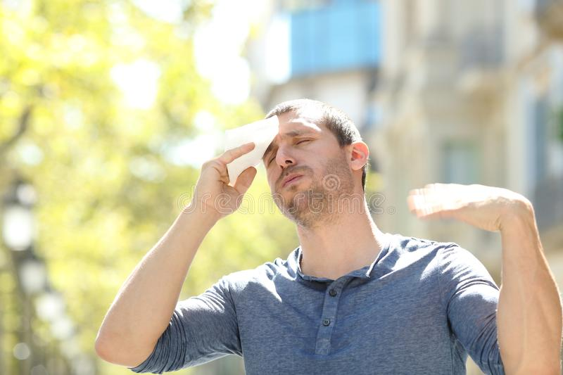 Stressed man sweating suffering heat stroke a warm day. Stressed man sweating and drying with a wipe suffering heat stroke a warm day in summer in the street stock photos