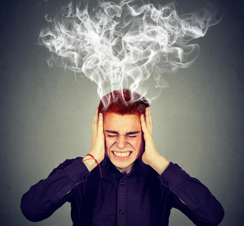 Stressed man thinks intensely having headache. Stressed man thinks very intensely having headache isolated on gray wall background stock images