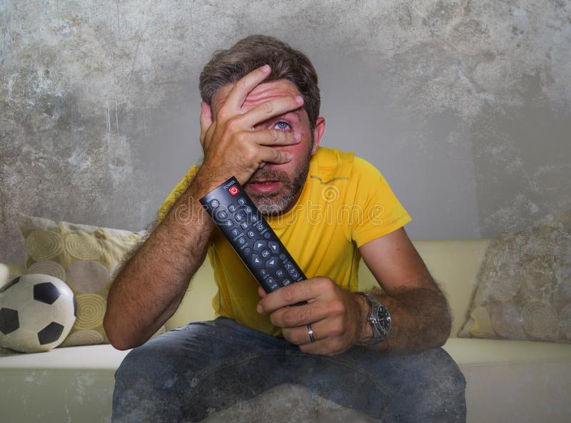 Stressed man watching football game on TV sitting at home living room couch excited and with expression of crazy intense emotion. 30s to 40s attractive and royalty free stock photography