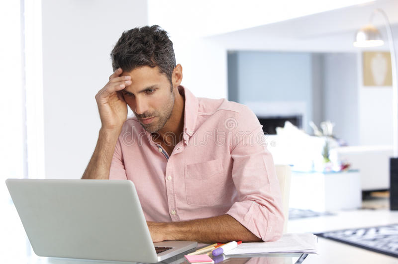 Stressed Man Working At Laptop In Home Office stock photography
