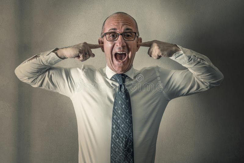 Stressed manager screaming with his fingers in his ears stock images