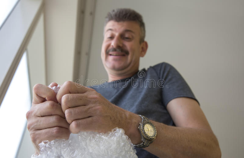 Middle aged man popping bubble wrap. Stressed middle aged man popping bubble wrap royalty free stock photography