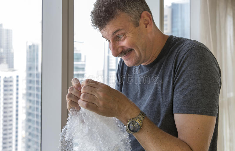 Middle aged man popping bubble wrap. Stressed middle aged man popping bubble wrap royalty free stock photos