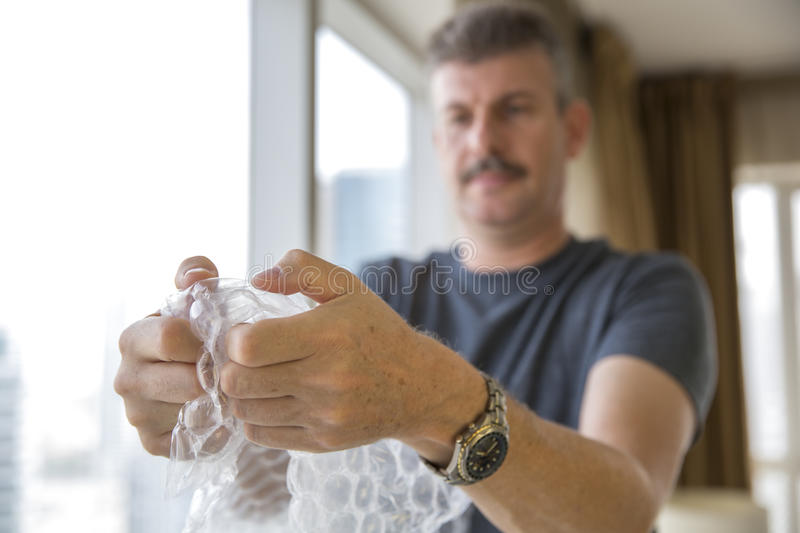 Middle aged man popping bubble wrap. Stressed middle aged man popping bubble wrap stock images