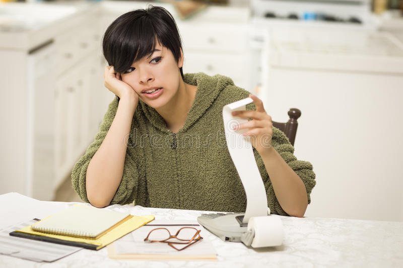 Stressed Multi-ethnic Young Woman Agonizing Over Financial Calculations royalty free stock image