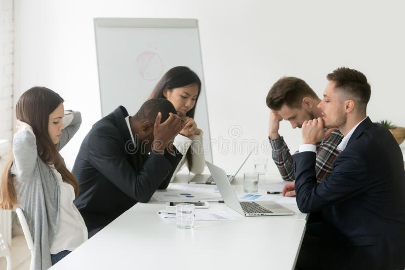 Stressed multiracial team thinking of problem solution at group. Stressed multiracial team thinking of problem solution at emergency office meeting, sad diverse stock photography