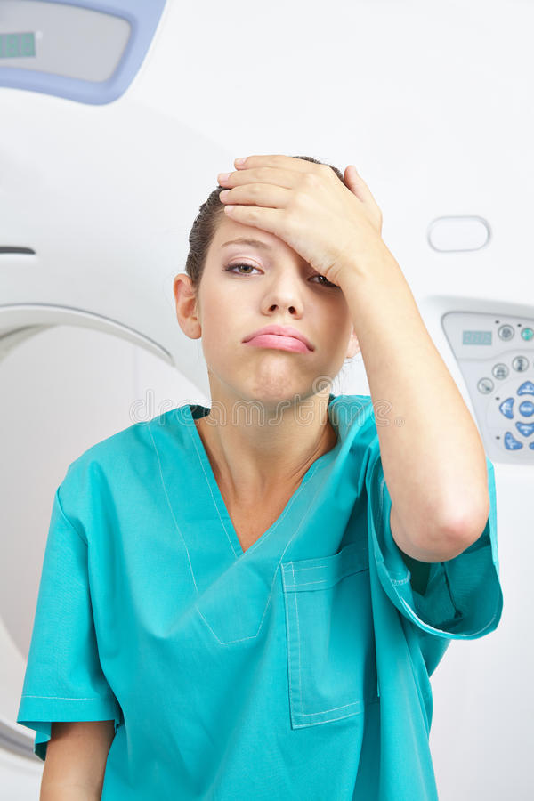 Stressed nurse with burnout in hospital. Young stressed nurse with burnout in hospital slapping her forehead stock photo