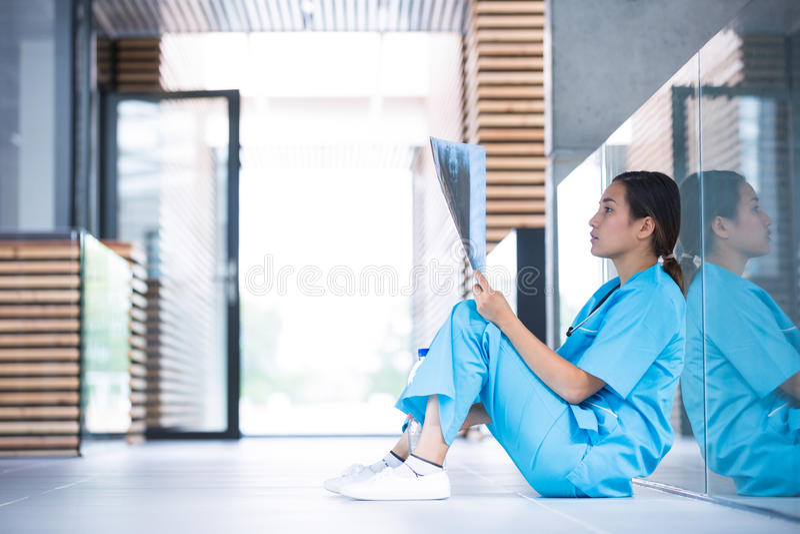 Stressed nurse examining X-ray report. In hospital corridor royalty free stock photo