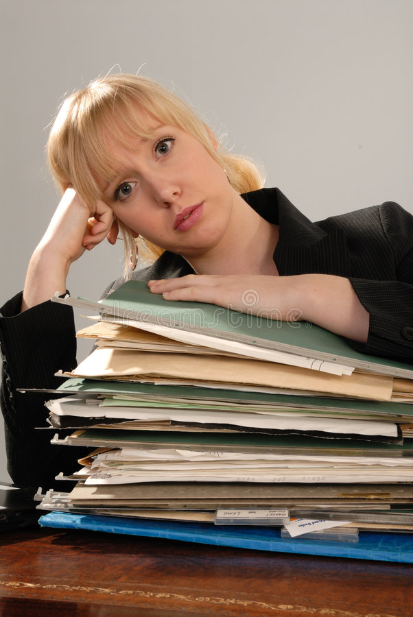 Stressed office executive with stack of paperwork stock photo