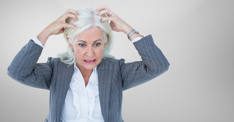Stressed older woman against grey background stock image