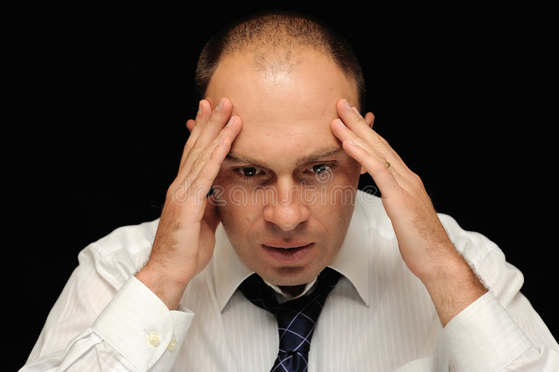 Stressed out business man. A stressed out or worried business man holding his head stock images