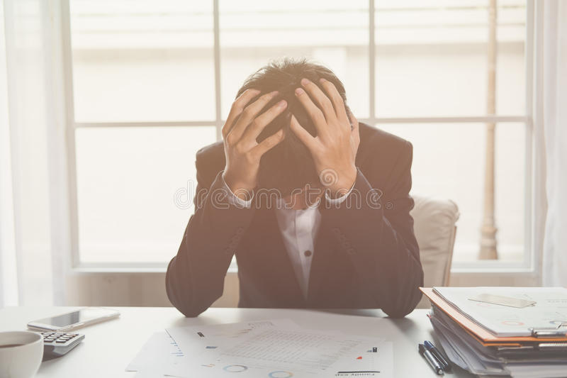 A stressed out business man holds his head in despair stock photo