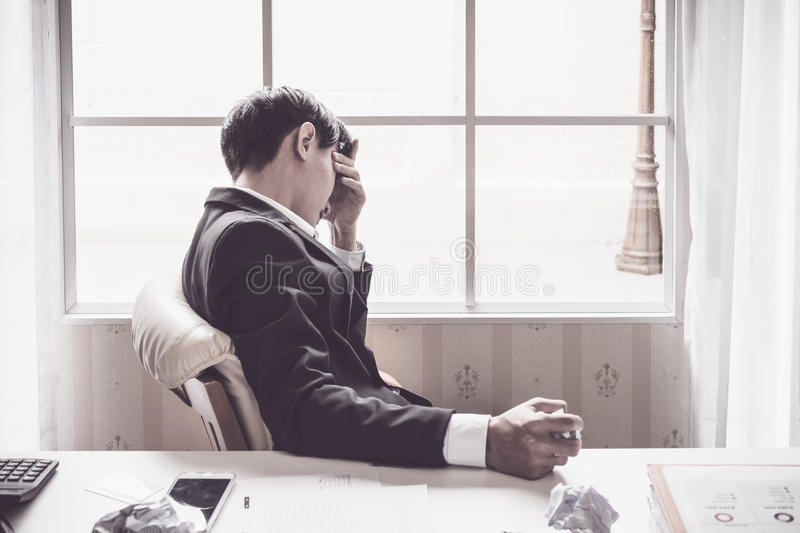 A stressed out business man holds his head stock image