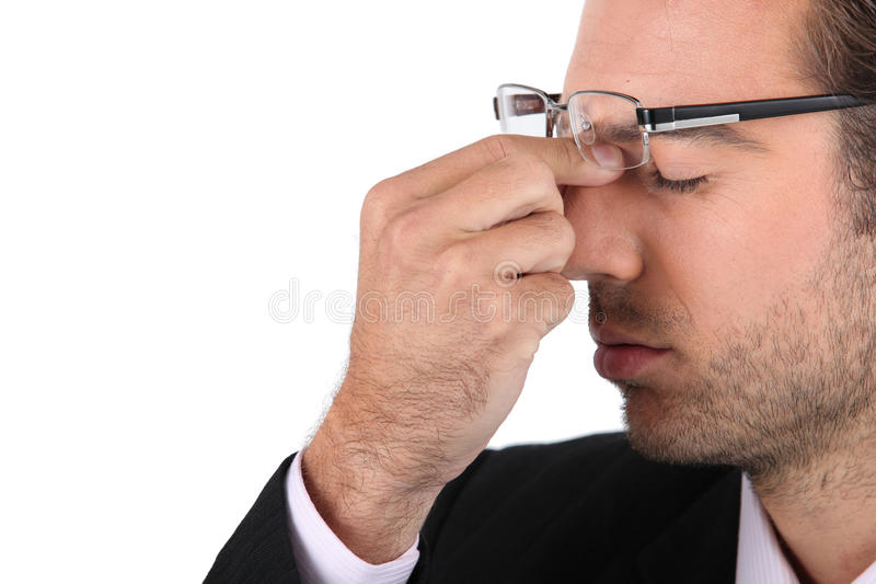 Stressed out businessman. A stressed out businessman touching glasses