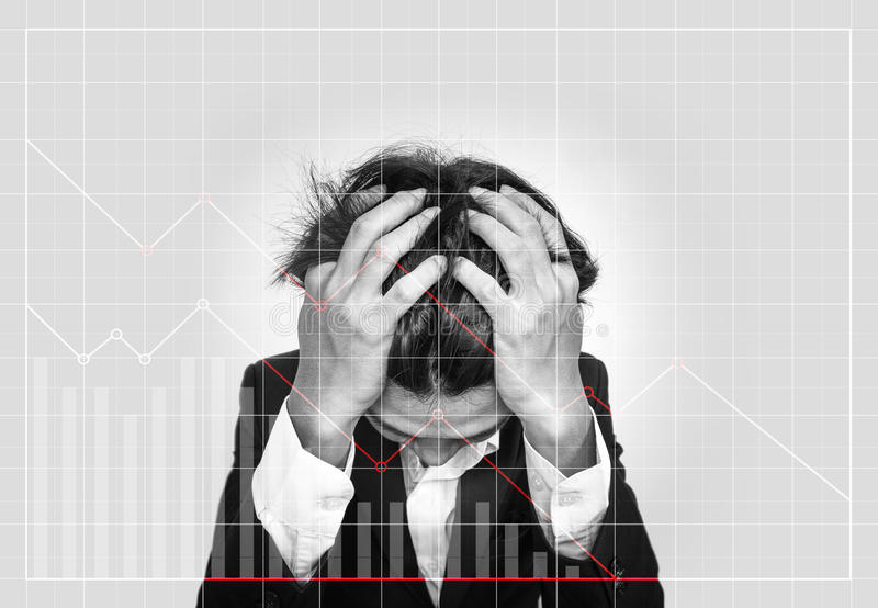Stressed out businessman, with downward business graphs. Failure stock market and loss business investment profit concepts. Stressed out businessman,with royalty free stock images