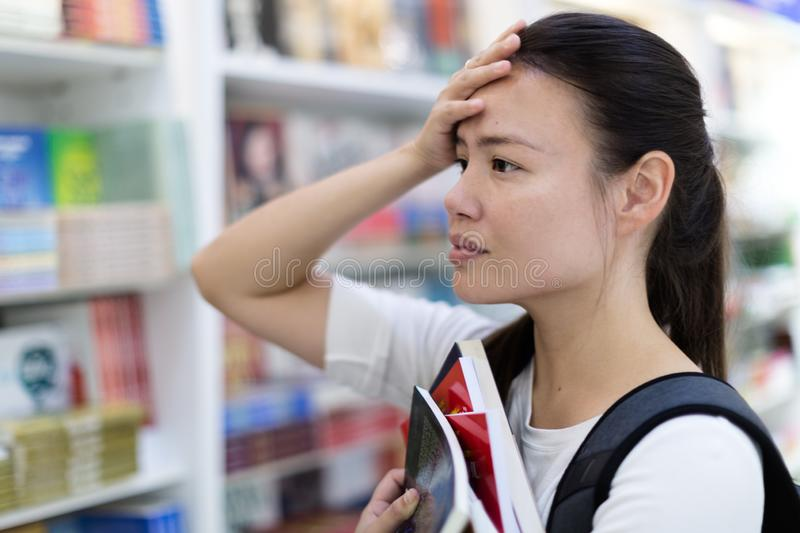 Stressed out female student searching for books in the library royalty free stock image
