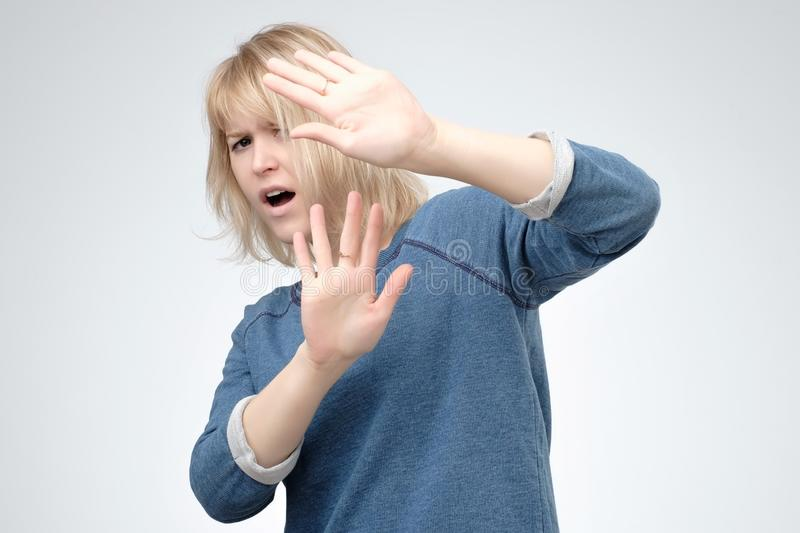 Stressed out woman keeping hands in stop gesture, trying to defend herself as if saying Stop that. Stay away from me stock photo