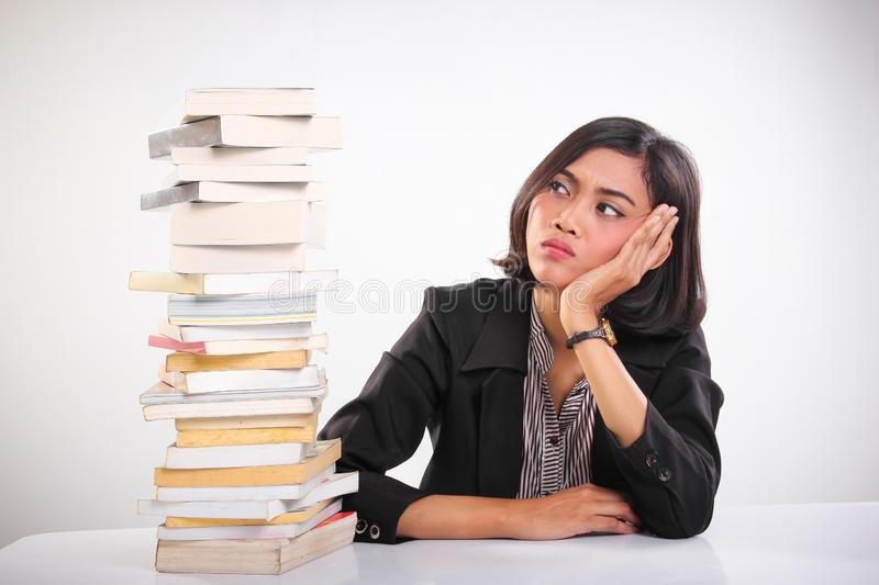 Stressed out young woman feels overwhelmed looking at stack of textbooks stock photos