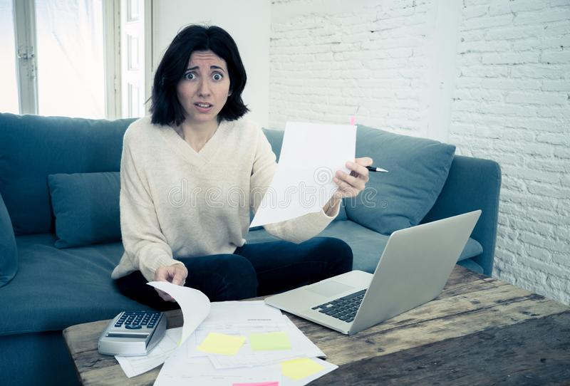 Stressed and overwhelmed young woman trying to manage home finances paying bills feeling desperate stock photo