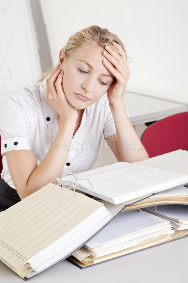 Stressed and overworked young businesswoman royalty free stock photo
